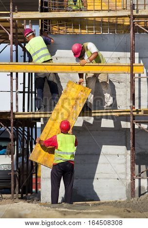 Construction Workers Placing Formworks