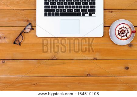 Overhead view of laptop keyboard next to coffee and spectacles on wooden slatted background
