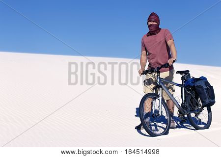 Travel by bike in the desert with a backpack and tent.