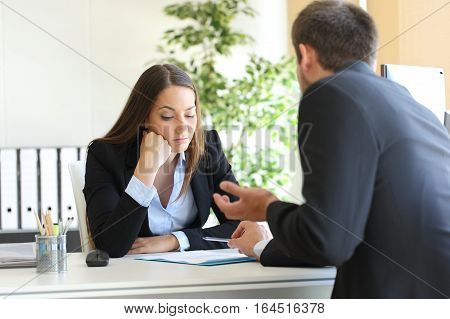 Bad salesman trying to convince to a bored client in her office or businessman in a job interview