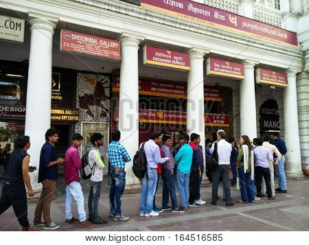 Delhi, India - 26th Nov 2016: People stand in a queue outside a bank ATM in Connaught Place Delhi post banning of the Rs.500 and Rs.1000 currency notes