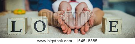 Baby feet in mother hands. Tiny Newborn Baby's feet on female Heart Shaped hands closeup. Mom and her Child. Happy Family concept. Beautiful conceptual image of Maternity. Newborn baby feet in hands