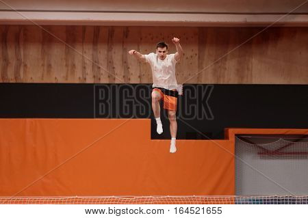 Young athlete on the trampoline in the graceful flight.