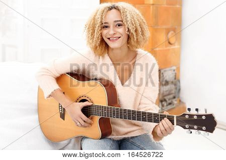 The joy that comes from musicRelax while playing the guitar. Girl playing the guitar. The girl guitar tunes.