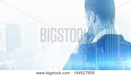 Back view of thoughtful businessman on city background. Double exposure. Research concept