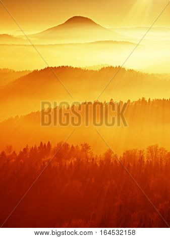 Red filter photo. Red daybreak. Misty daybreak in a beautiful hills. Peaks of hills are sticking out from foggy background the fog is red and orange