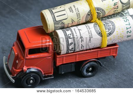The toy red lorry with coins in a body on a stone background