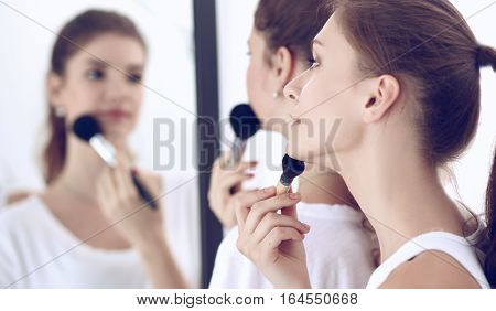 Beautiful girl looking in the mirror and applying cosmetic with a big brush.