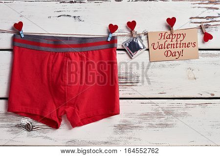Red boxer briefs on rope. Condom near Valentine's Day card. Precaution helps to be healthy.