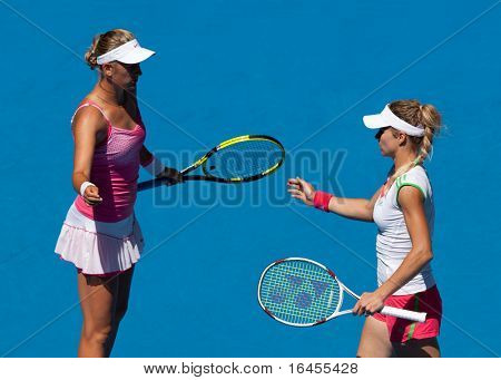 MELBOURNE - JANUARY 28: Maria Kirilenko of Russia (R) with partner Victoria Azarenka of Belarus in the women's doubles final at the Australian Open on January 28, 2011 in Melbourne, Australia
