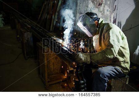 electric welding. electric welder welds metal parts factory