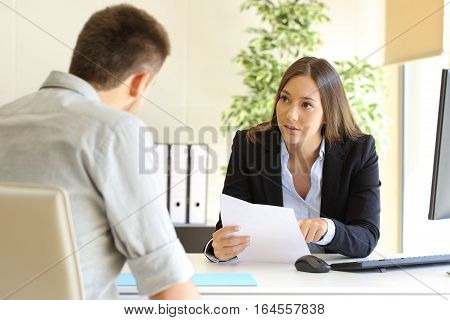 Guy and businesswoman talking in a job interview in an office
