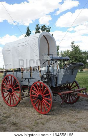 Vintage pioneer covered wagon displayed outdoors for tourist.