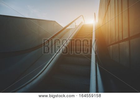 City outdoor grungy modern escalator goes up to sun and teal sky rusty metal tiled wall on the right view from the rail Barcelona Spain