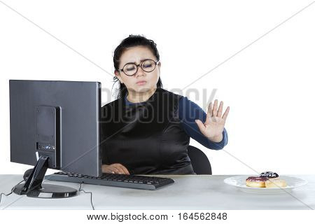 Image of young businesswoman working with computer and refusing donuts on the plate while sitting in the studio