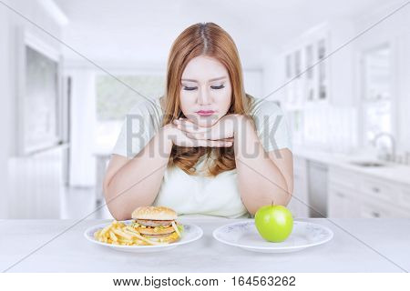 Picture of blonde woman looks confused to choose a fresh apple fruit or hamburger shot in the kitchen