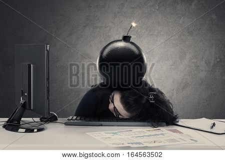 Frustrated entrepreneur sleeping on the desk with bomb over her head concept of financial bankrupt