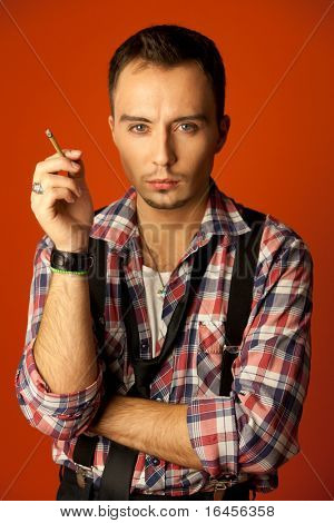 Celebrity resemblance. Johnny Deep lookalike. Stylish young man with cigarette wearing checkered shirt and suspenders.