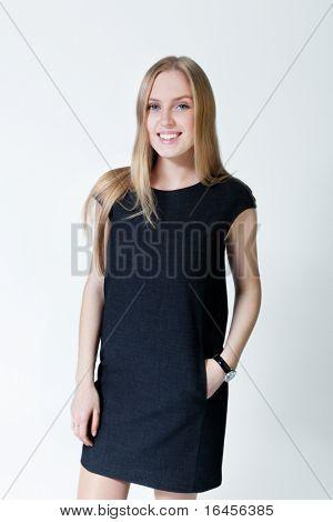 Happy smiling blonde wearing fashionable dress. Fresh new young face. Studio shot, uniform background.