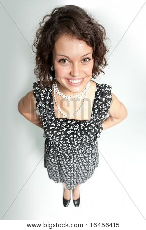 Funny smiling curly beauty! Top view to the pretty girl wearing spotted dress.