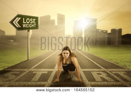 Portrait of a pretty woman with overweight body preparing to run on the start line with text of lose weight on the signpost