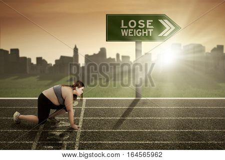 Young woman wearing sportswear and ready to run on the track with a text of lose weight on the signpost