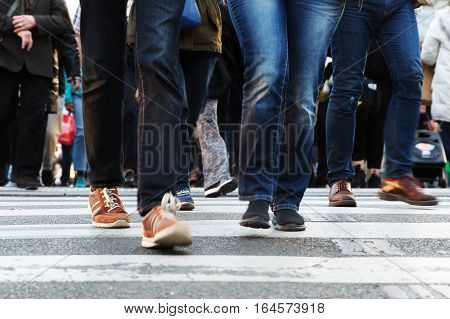 legs of people crossing a street in the city