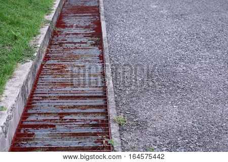 water drain or ditch metal grid on the road