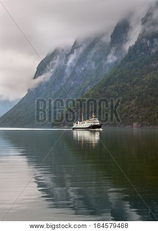 Norway Geiranger fjord . On the banks are located cliffs up to 1400 meters and glaciers .The main means of transportation in the country of fjords - ferries.