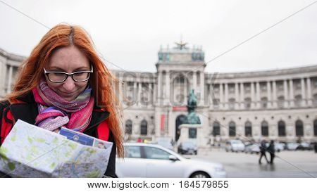 Yong tourist - woman with red hair and glasses looking map in Heldenplatz, Vienna, close up