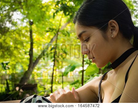 Asian woman sitting on the wooden chair in the garden