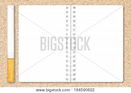 Cigarette tobacco and notebook paper page on cork board background for design with copy space for text or image.