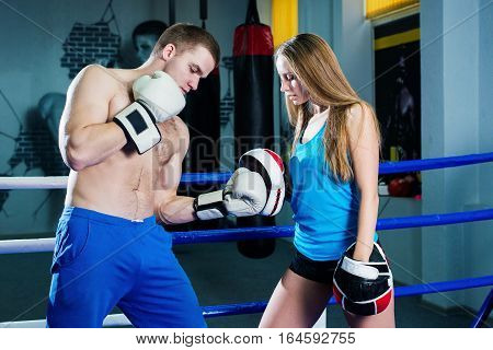 Male and female sporty couple practicing boxing at the gym at boxing ring
