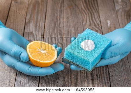 cleaning tools and sodium bicarbonate in hand on wooden table