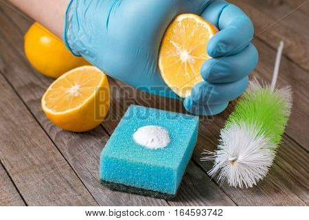 Eco-friendly natural cleaners baking soda lemon and cloth on wooden table in hand on wooden table