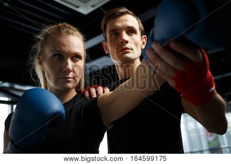 Training of young girl with coach in gym