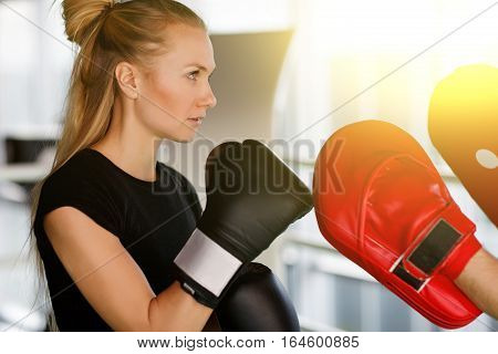 Girl engaged in boxing with coach in gym