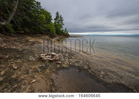 Campfire Ring And Backcountry Campsite On Lake Superior Beach. Stone campfire ring and backcountry campsite on the rocky coast of Lake Superior in Michigan's Upper Peninsula.