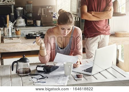 Caucasian Family Having Hard Time Paying Bills. Young Woman Reading Document With Concentrated Look,