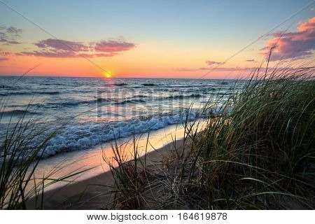 Tranquil Sunset Beach Background.  Beautiful sunset horizon over water with a sandy beach and dune grass in the foreground. Hoffmaster State Park. Muskegon, Michigan.