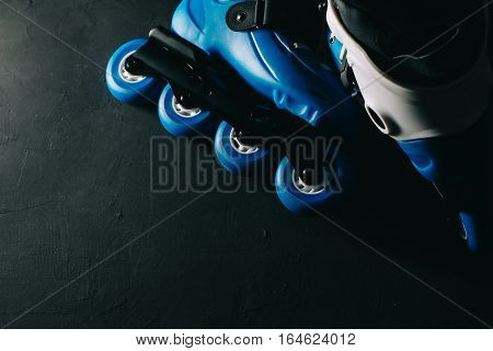 Close up view of blue roller skates inline skate or rollerblading on dark tinted grunge backgroung. Street culture, sports equipment