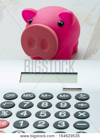 a pink piggy bank and a calculator