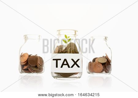 Coins in glass bottles on a white table. Saving for Taxes Concept.