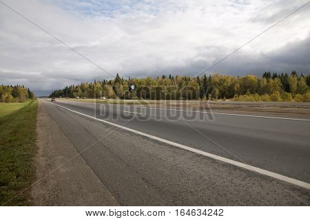Direct suburban highway with a speed limit sign 130 km / h and passing vehicles in the early autumn