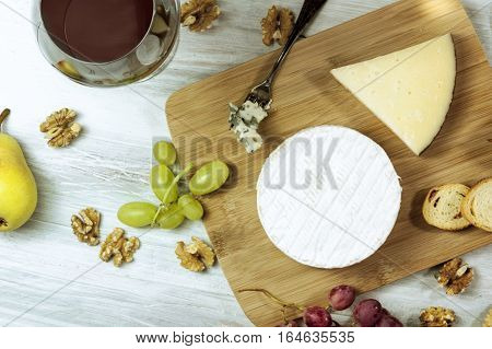 A photo of a selection of cheeses, with a round of Camembert in the centre and some more varieties around it, as well as grapes, nuts, and pieces of bread, with a glass of red wine