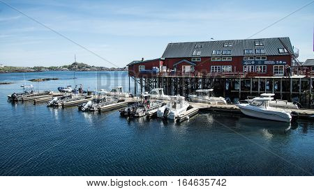 Reine, Norway - June 2, 2016: Traditional fishing boat with red rorbu fishing houses on Lofoten islands in Norway