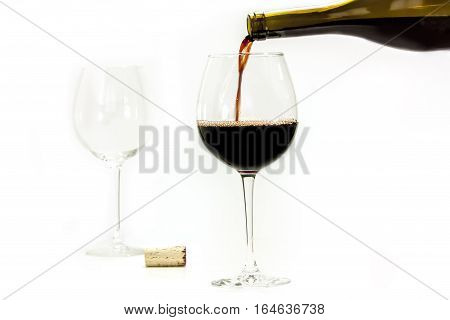 Red wine poured from a bottle into a glass, with an empty, almost transparent, glass in the background, and a cork. Selective focus, white background