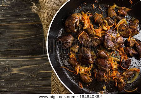 Fried chicken livers and hearts with vegetables in a frying pan