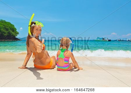 Happy family - mother with baby girl have fun in beach pool with sea surf. Travel healthy lifestyle people water sport outdoor activity swimming lessons and snorkeling on summer holidays with child
