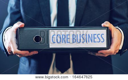 Core business with businessman and document ring binder primary area or activity that company focuses on in its operations.